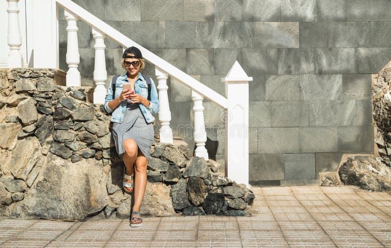 Молодая женщина используя smartphone на положении перемещения - фасонируйте блоггер стоковые изображения rf