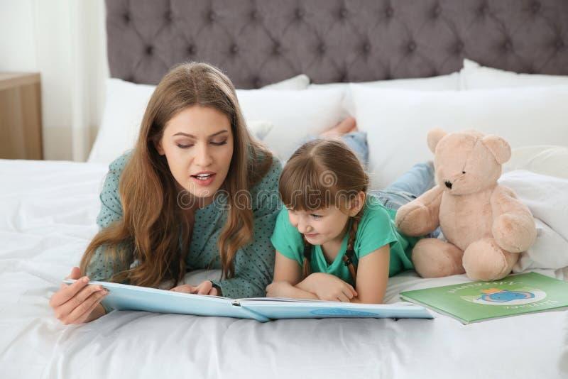 Молодая женщина и ее книга чтения дочери Помогать выучить стоковое изображение