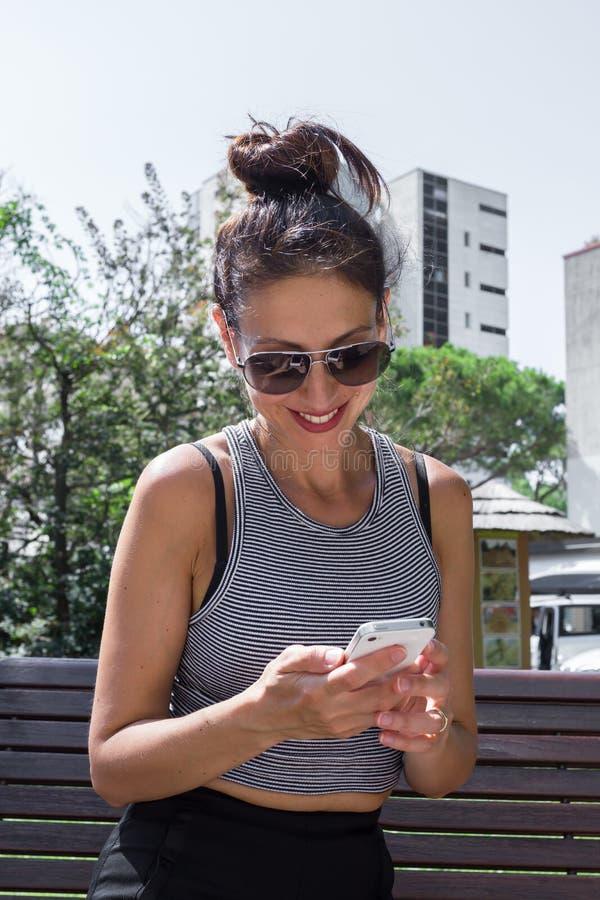 Молодая женщина и ее smartphone стоковые изображения rf