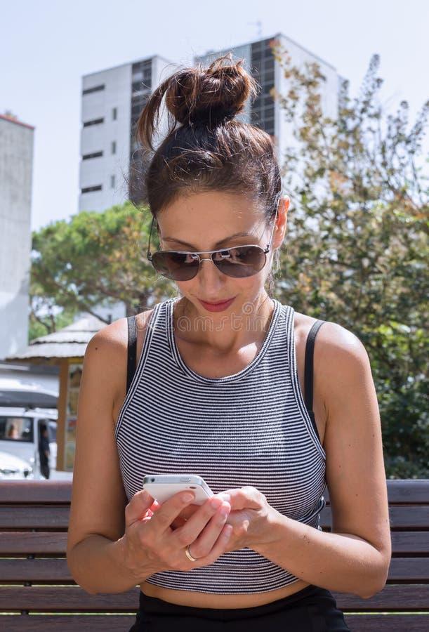 Молодая женщина и ее smartphone стоковые фотографии rf