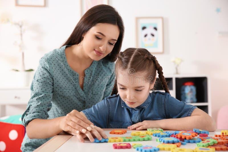 Молодая женщина и маленькая девочка с аутистический играть разлада стоковые фотографии rf