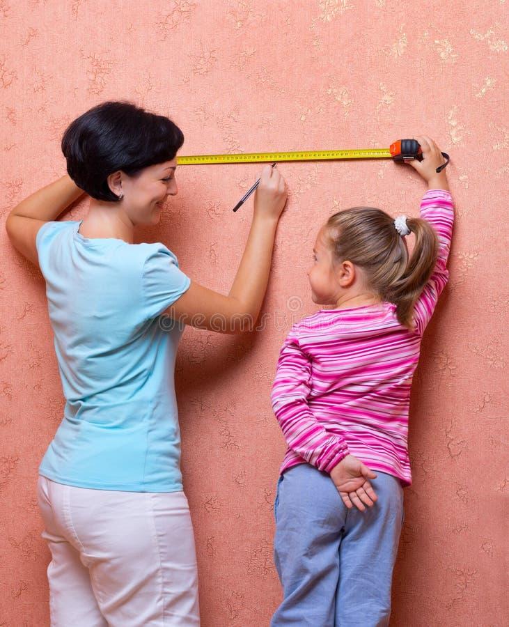 Молодая женщина и маленькая девочка с измеряя лентой стоковые изображения rf