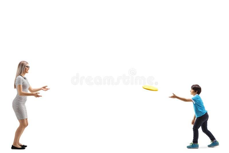 Молодая женщина и мальчик играя с frisbee стоковая фотография rf