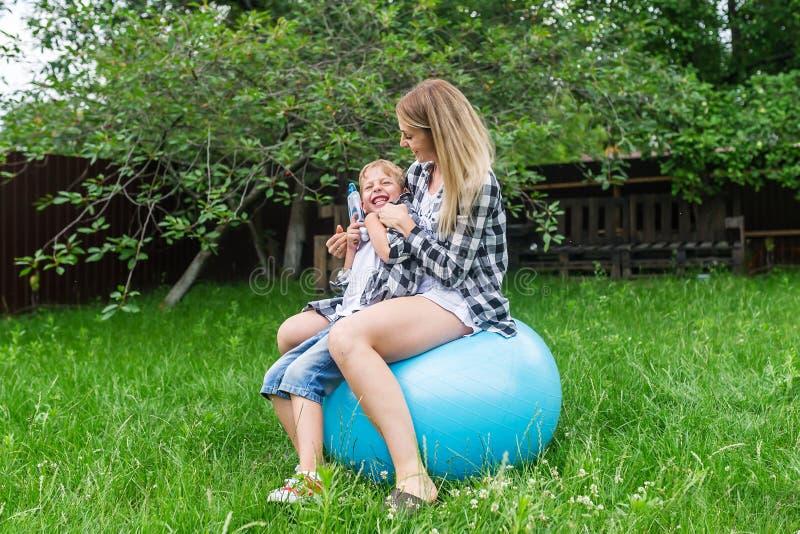Молодая женщина и мальчик скача на голубой раздувной шарик на лужайке стоковая фотография