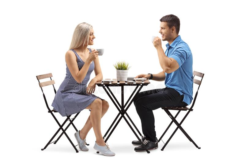 Молодая женщина и молодой человек сидя на журнальном столе стоковая фотография rf