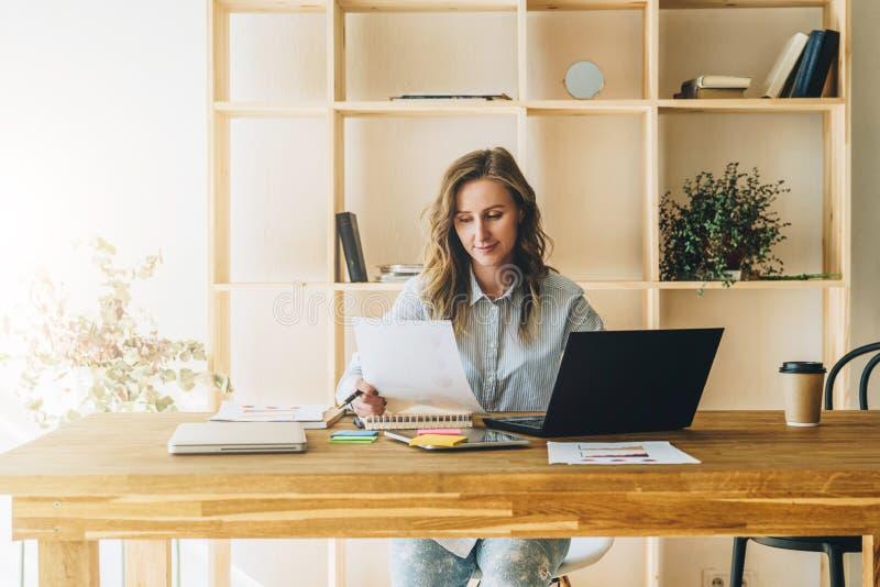 Молодая женщина коммерсантки сидит на кухонном столе, читая документы, компьтер-книжка польз, деятельность, изучая стоковые фото