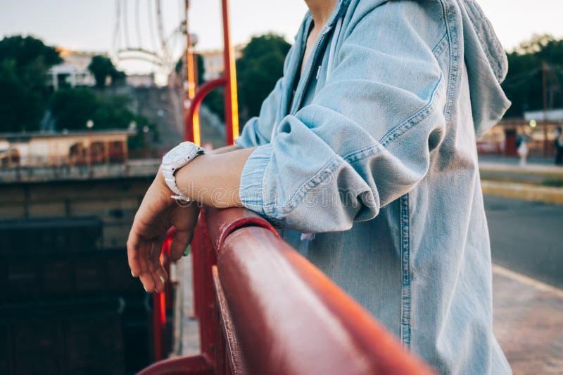 Молодая женщина конца-вверх в положении куртки джинсов рядом с мостом стоковая фотография