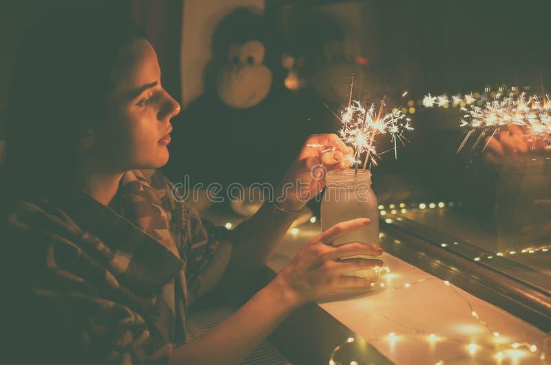 Молодая женщина которая освещает фейерверки дома стоковое изображение