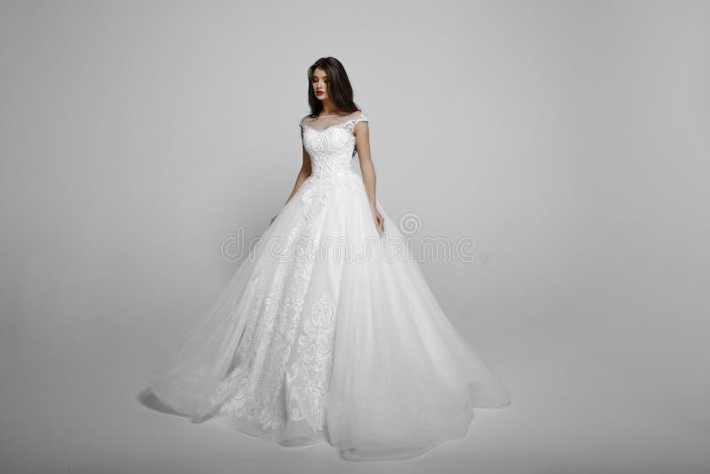 Молодая женщина красоты в платье длинной белой принцессы wendding, с составляет, представляет стоять, isolaetd на белой предпосыл стоковые фотографии rf