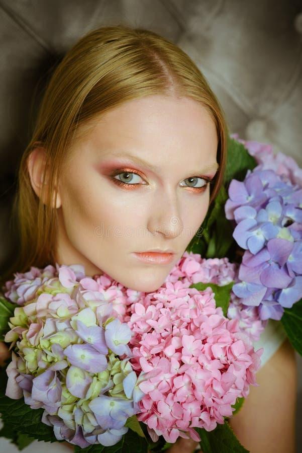 Молодая женщина красоты, светлые волосы с гортензией стоковое фото rf