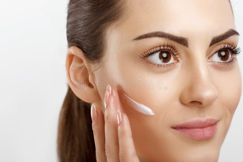 Молодая женщина крупного плана красоты счастливая приложить сливк к ее стороне Skincare и концепции косметик r Забота кожи сторон стоковые изображения