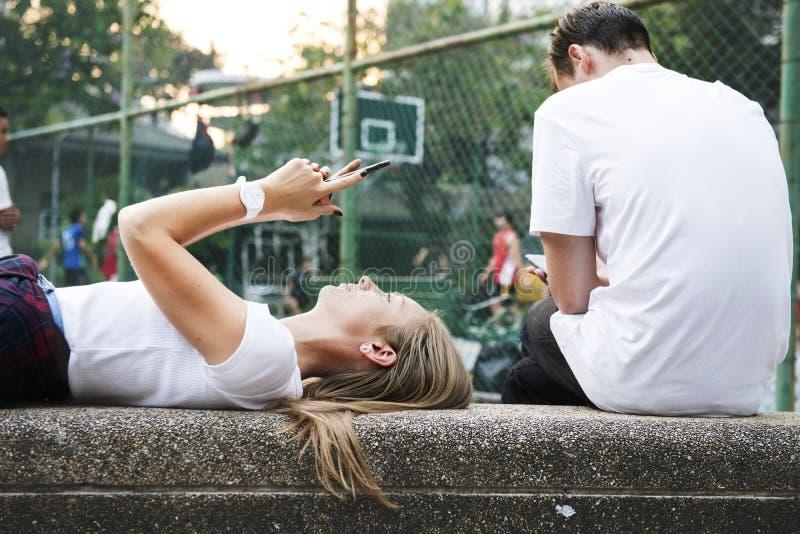 Молодая женщина лежа вниз в парке используя smartphone с другим человеком стоковое изображение rf