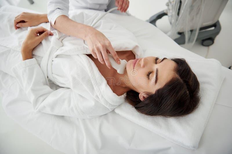 Молодая женщина лежа на кушетке во время медицинского осмотра стоковое изображение