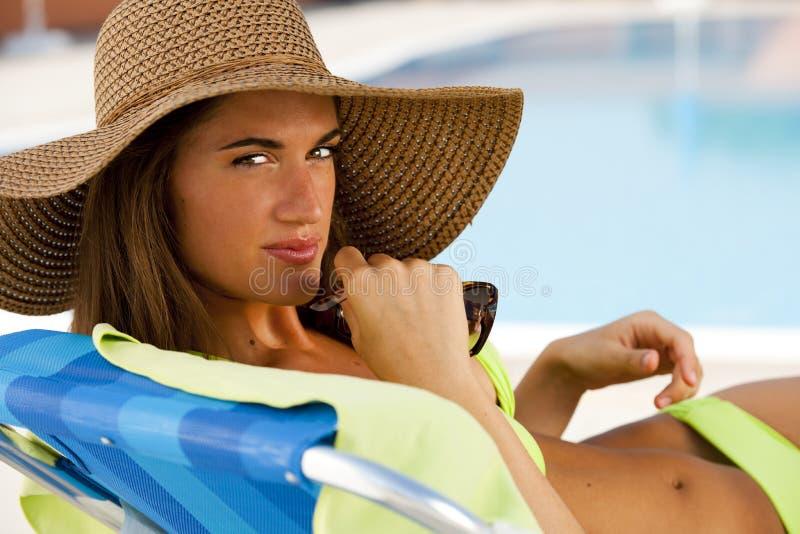 Молодая женщина лежа на deckchair плавательным бассеином стоковые фотографии rf
