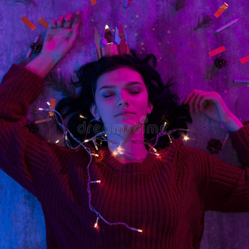 Молодая женщина лежа со светами торжеством xmas накаляя, рождеством, Новым Годом стоковые фото