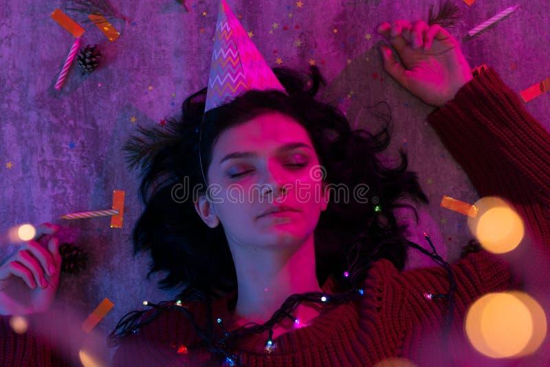 Молодая женщина лежа со светами торжеством xmas накаляя, рождеством, Новым Годом стоковая фотография