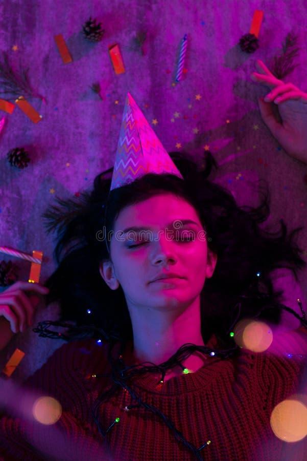 Молодая женщина лежа со светами торжеством xmas накаляя, рождеством, Новым Годом стоковое изображение