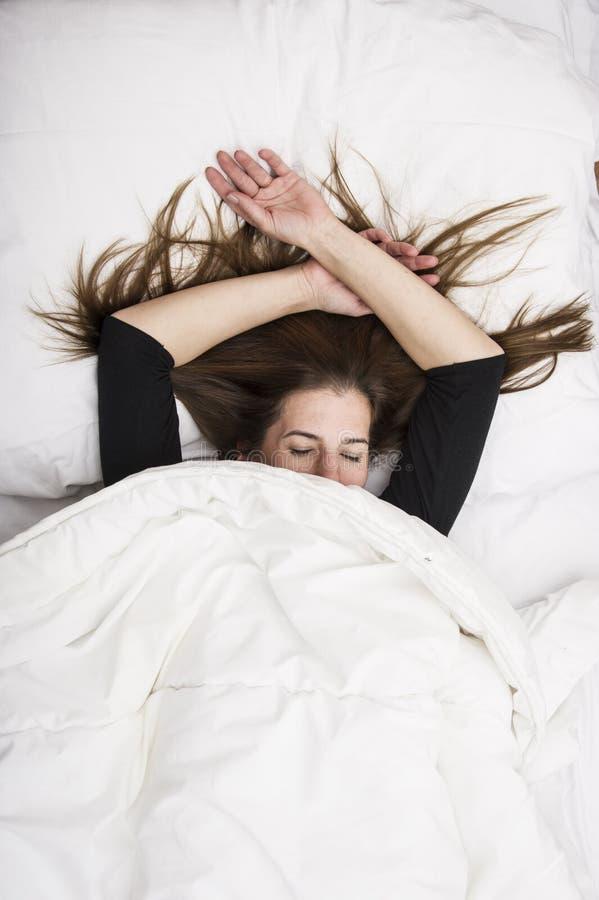Молодая женщина лежит в ее кровати при закрытые глаза, усмехаясь под ее одеялом после restful сна стоковая фотография