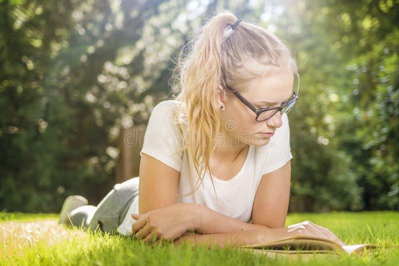 Молодая женщина лежит на траве в парке и смотрит в книге стоковые изображения