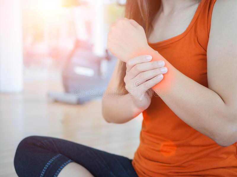 Молодая женщина массажируя ее запястье руки после разработки или раненое стоковые фотографии rf