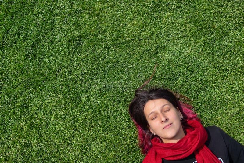 Молодая женщина мечтая на зеленой траве с закрытыми глазами стоковые фото