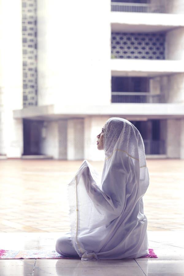 Молодая женщина молится Аллаху в мечети стоковая фотография