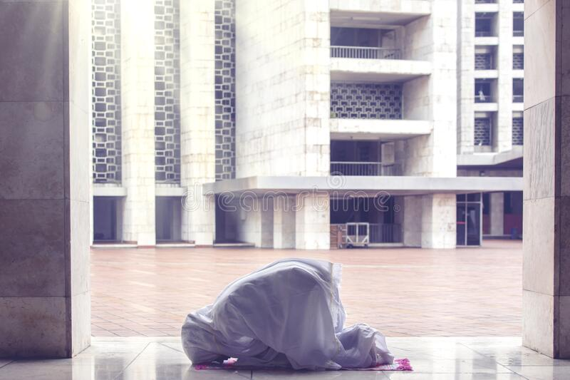 Молодая женщина молится Аллаху в мечети стоковые фото