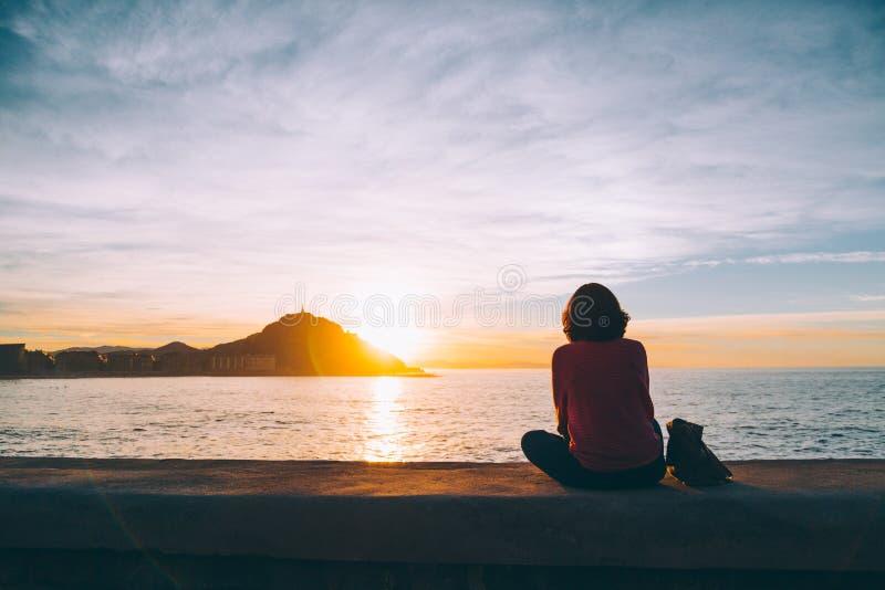 Молодая женщина наблюдая заход солнца над морем в San Sebastian стоковые изображения rf