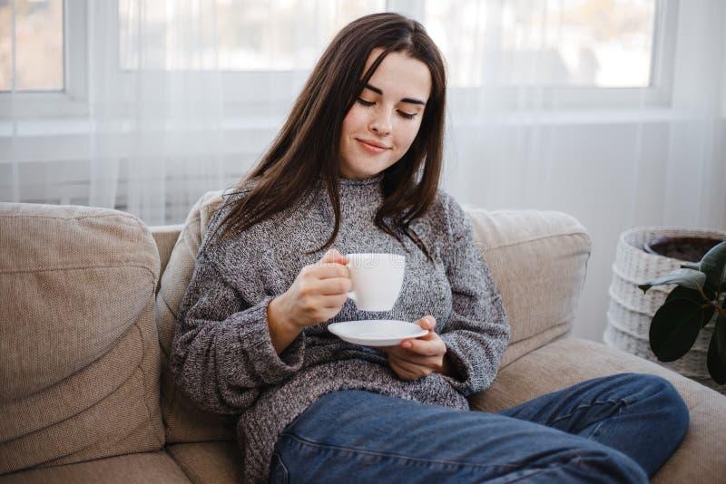 Молодая женщина наслаждается кофе утра в живущей комнате стоковые изображения rf