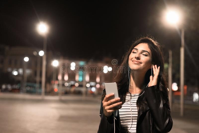 Молодая женщина наслаждаясь музыкой в наушниках, идя в город ночи стоковое изображение