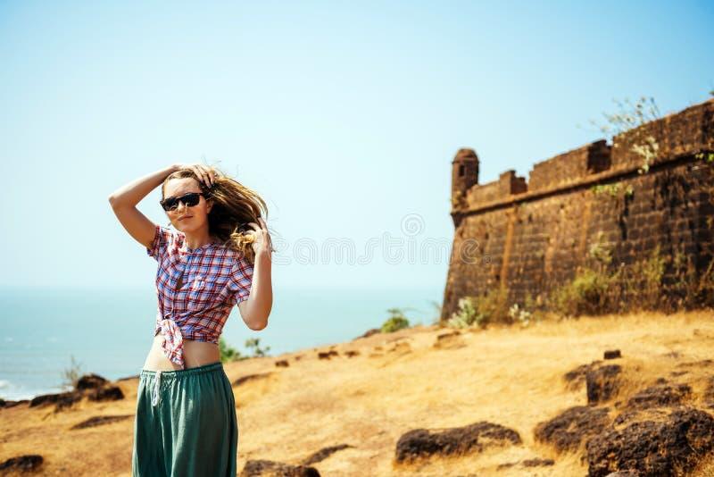 Молодая женщина наслаждаясь призванием около старого индийского форт стоковые фотографии rf