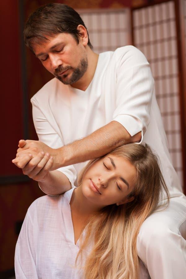 Молодая женщина наслаждаясь профессиональным тайским массажем стоковые изображения rf