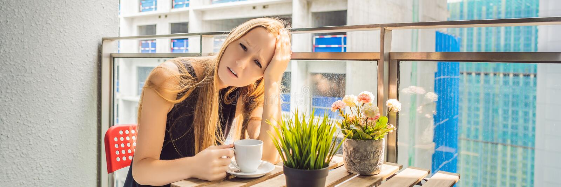 Молодая женщина на балконе надоеданном работами здания снаружи Концепция шума Загрязнение воздуха от ЗНАМЕНИ пыли здания стоковое фото