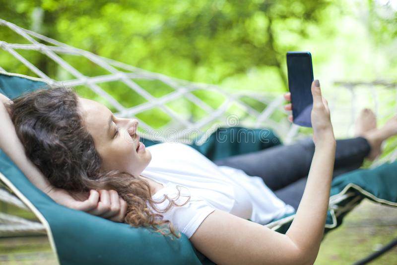 Молодая женщина на гамаке используя смартфон стоковая фотография rf
