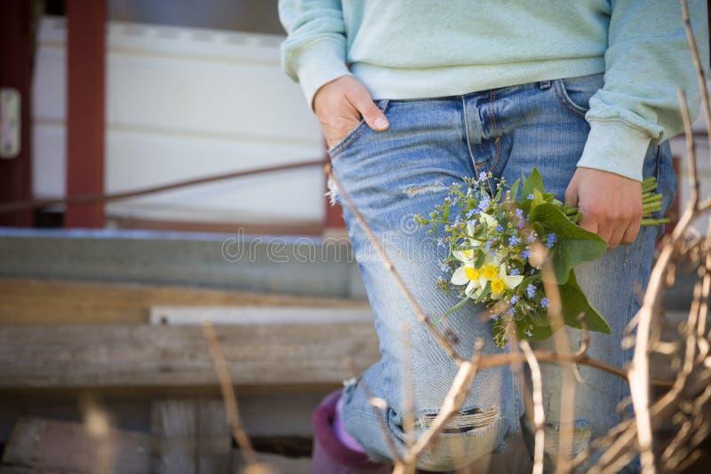 Молодая женщина на голубых джинсах держа красивый сад цветет в ее руке Букет лета в руке ` s девушки напольно Сад p весны стоковое фото rf