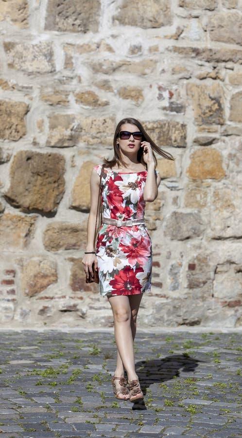 Молодая женщина на идти телефона стоковые изображения rf