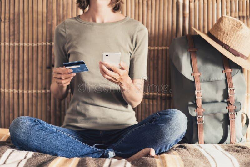 Молодая женщина на каникулах используя смартфон и кредитную карточку Онлайн концепция покупок и перемещения стоковое изображение