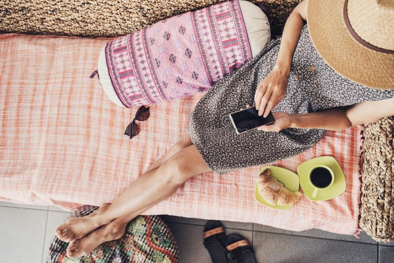 Молодая женщина на каникулах используя умный телефон стоковое фото