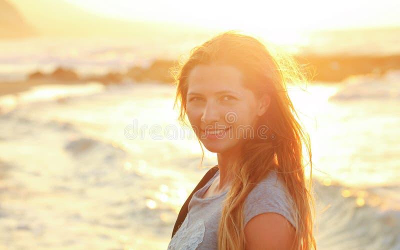 Молодая женщина на пляже во время захода солнца, сильного освещает море контржурным светом в предпосылке, детали на ее усмехаясь  стоковая фотография