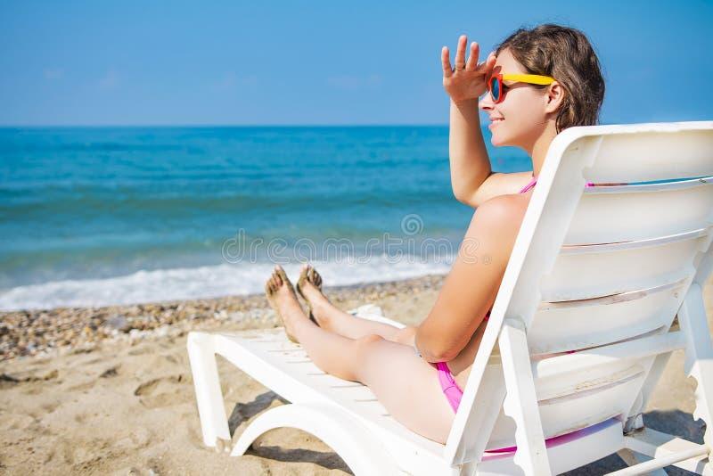 Молодая женщина на пляже моря сидит на deckchair и смотрит в расстояние девушка в курорте лета тропическом ослабляет на пляже стоковое изображение rf