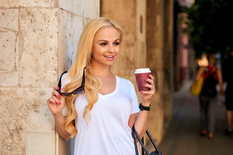 Молодая женщина на стене на улице с кофе стоковые фото