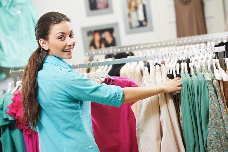 Молодая женщина на ходить по магазинам одежд рубашек стоковое изображение