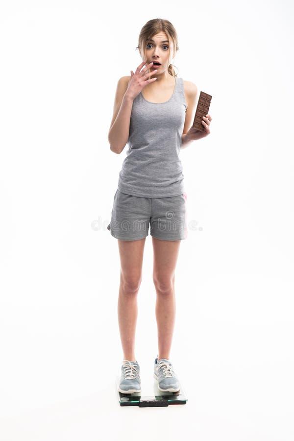 Молодая женщина несчастная с ее весом держа шоколад, изолированный на белизне стоковое фото rf