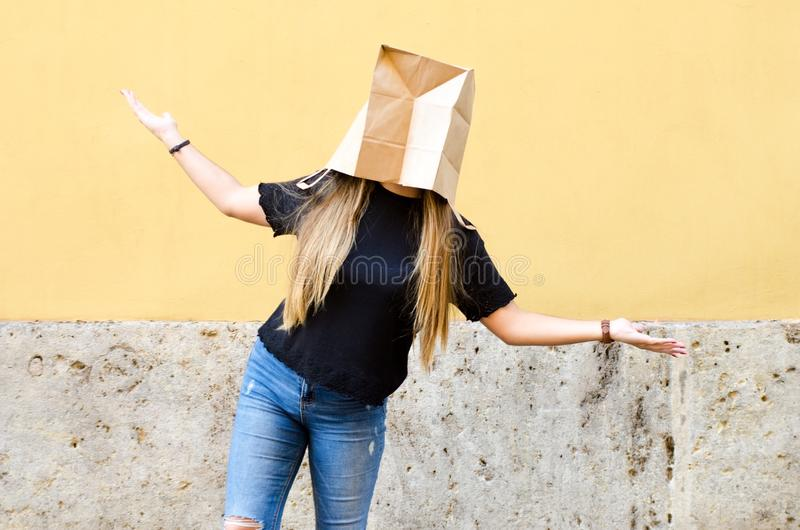 Молодая женщина нося бумажный мешок над ее головой перед желтым цветом стоковая фотография rf