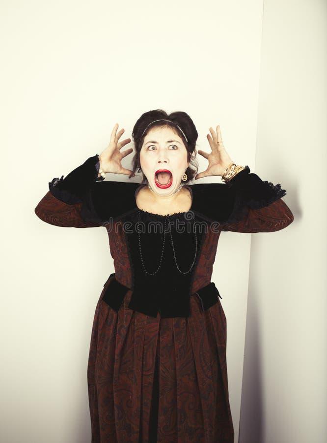 Молодая женщина нося елизаветинский костюм и кричащее с ее руками к ее голове стоковые фотографии rf