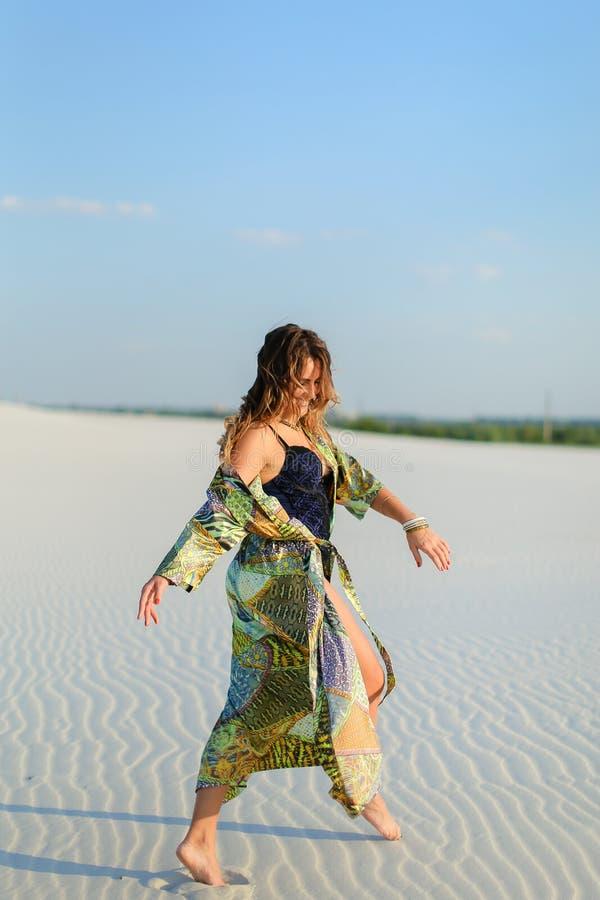 Молодая женщина нося зеленую робу пляжа и черное положение купальника стоковые фото