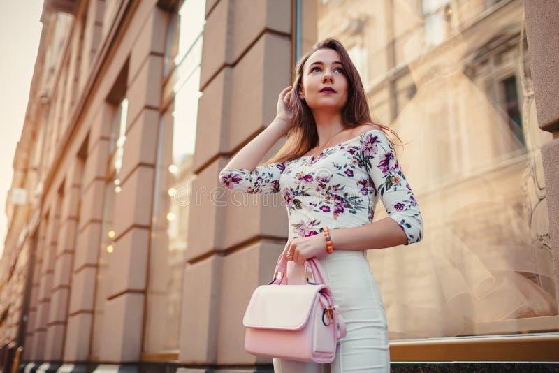 Молодая женщина нося красивые обмундирование и аксессуары outdoors Девушка держа сумку Фотомодель идя в город стоковое фото rf