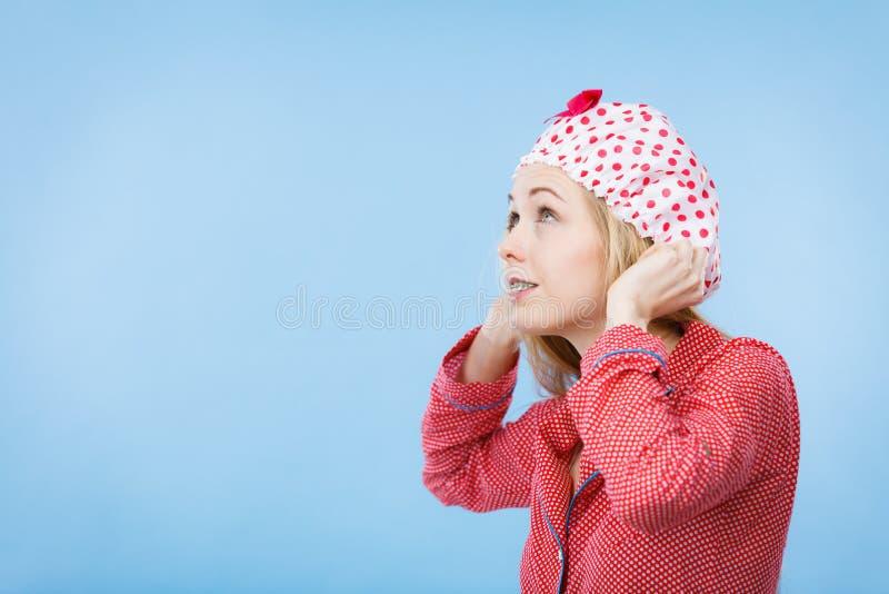 Молодая женщина нося розовые пижамы кладя купая крышку стоковое изображение