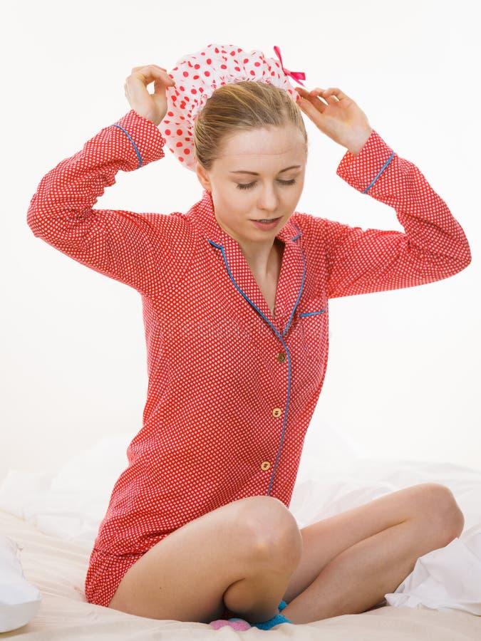Молодая женщина нося розовые пижамы кладя купая крышку стоковое фото rf