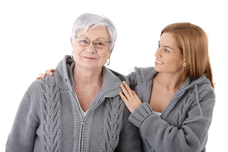 Молодая женщина обнимая старший усмехаться мати стоковая фотография